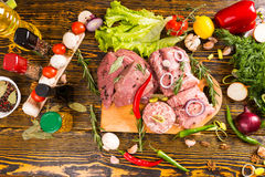 Cluttered table of various meats and veggies Stock Images
