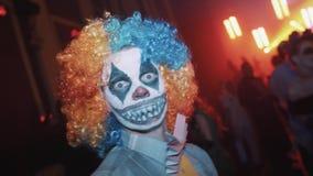 Clwn asustadizo que mira directamente in camera el partido de Halloween del club de noche almacen de video