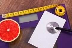 Cm på elektronisk badrumskala och den nya grapefrukten med stetoskopet, bantning och sunt livsstilbegrepp Royaltyfri Bild