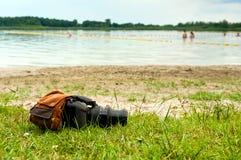Cámara y mochila en orilla del lago Fotos de archivo