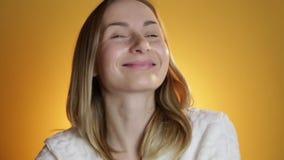 Câmera de vista feliz de sorriso da jovem mulher bonita em um fundo amarelo filme