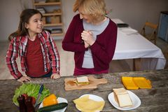 Beautiful grandma and granddaughter are making sandwiches. Cmiling grandma and granddaughter looking at each other. Cooked sandwich together Stock Photography