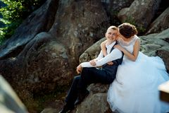 Cmiling hugging newlywed couple are looking at each other while sitting on the rock. Close-up wedding portrait. Cmiling hugging newlywed couple are looking at Royalty Free Stock Images