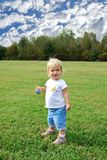 Cmon play. Toddler girl standing in park Royalty Free Stock Images