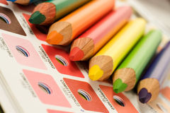 Cmyk color bars with colour pencils. Orange, red, yellow, green and blue pencils on cmyk color bars Stock Images