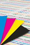 CMYK color chips. Color chips in Cyan, Magenta, Yellow and Black on printed texts by inkjet printer Royalty Free Stock Photos