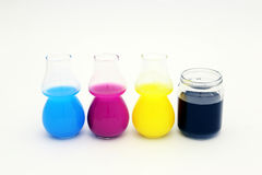 CMYK Concept. Colored ink in glass, cyano magenta yellow and black royalty free stock photos