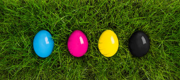 CMYK easter eggs. Lying in grass Royalty Free Stock Photos