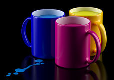 CMYK mugs. Three colored mugs with a cyan, magenta and yellow inks Stock Photography