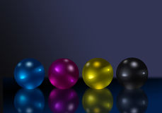Cmyk reflective balls. Reflective balls in four color printing process colors on dark reflective background Royalty Free Stock Photography