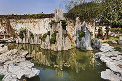 CN Suzhou Garden mini rocks. Mini rock formation from still water pond in a public garden of Suzhou city in China on a bright sunny autumn day Royalty Free Stock Photo