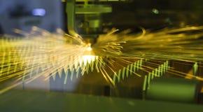 从CNC工业激光切口钢金属的明亮的火花 免版税库存照片