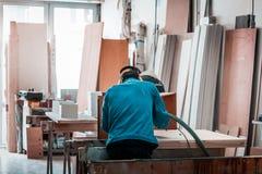 Cnc木切口机械,有蓝色衬衣工作的操作员 库存图片