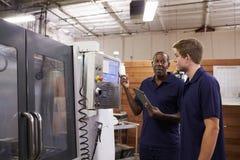 CNC机器的工程师训练男性学徒 免版税库存照片