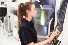 Θηλυκός μηχανικός που ενεργοποιεί CNC τα μηχανήματα στο πάτωμα εργοστασίων Στοκ Φωτογραφία