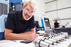 工程师与CNC机械的计划项目在背景中 图库摄影