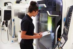 Θηλυκός μηχανικός που ενεργοποιεί CNC τα μηχανήματα στο πάτωμα εργοστασίων Στοκ εικόνα με δικαίωμα ελεύθερης χρήσης