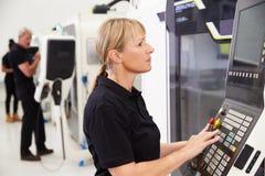 Θηλυκός μηχανικός που ενεργοποιεί CNC τα μηχανήματα στο πάτωμα εργοστασίων Στοκ Εικόνες