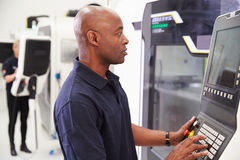 操作在工厂地板上的男性工程师CNC机械 免版税库存图片