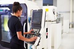 Θηλυκός μηχανικός που ενεργοποιεί CNC τα μηχανήματα στο πάτωμα εργοστασίων Στοκ Φωτογραφίες