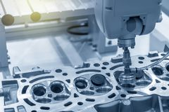 The CNC bore machine boring the intake and exhaust valve port at cylinder head . The engine part overhaul process by CNC machine royalty free stock photo