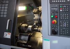 Cnc-Drehbank zieht Teil vom Metallwerkstückflaschenzug aus, moderne Drehbank für das verarbeitende Metall, Nahaufnahme, Industrie stockbild
