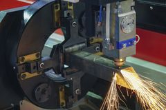 CNC fiber laser cutting machine cut the  stainless  tube. The CNC fiber laser cutting machine cut the  stainless  square pipe or tube with the sparking light.The Stock Photos