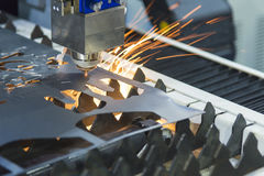 The CNC fiber laser cutting machine. Cutting the sheet metal with the sparking light.Hi-technology metal manufacturing concept stock images