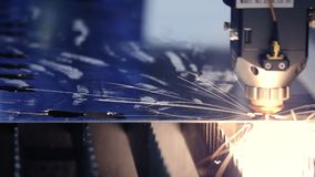 CNC Laser cutting of metal, modern industrial technology. Industrial laser cutter with sparks. The programmed robot head