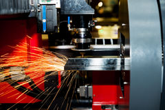 CNC laser cutting metal pipe with bright sparkle in factory. Ind stock photography