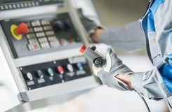 CNC Lathe Control Panel. Worker with Wired Remote Operating CNC Functions royalty free stock photography