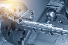 The CNC lathe machine cutting the slot at the shaft. By milling spindle stock image
