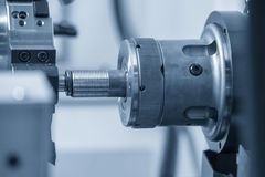 The CNC lathe machine cutting the thread    at the water pipe. The hi-technology  parts manufacturing process by turning machine royalty free stock image