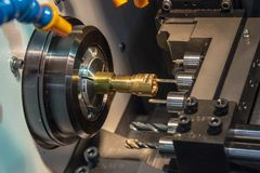 The CNC lathe machine drilling the hole on the brass  shaft part with drill tool. Hi-technology automotive part manufacturing process stock image