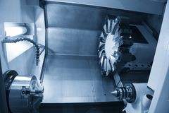The CNC lathe machine in the light blue scene. The modern machining process royalty free stock images