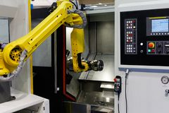 CNC lathe machine and robot. Used for automation of loading and unloading operations. Selective focus stock image