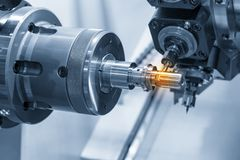 The CNC lathe machine or Turning machine. Cutting the slot at the steel shaft part.Modern manufacturing process stock photography