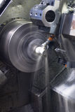 CNC lathe running with coolant. Long exposure of CNC lathe with cooling fluid on machined part stock image