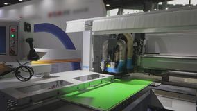 Cutting furniture blanks CNC machine. CNC machine on the stand in China. Cnc machine at the exhibition of hardware technology. CNC machine tool at work at the stock video footage
