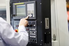 CNC machine operator working with a control panel. Selective focus royalty free stock photo
