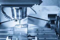 The CNC milling machine while cutting the sample work. Piece in blue-silver tone Royalty Free Stock Photos