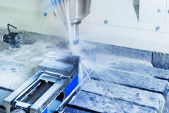 CNC milling machine during operation. Produced milling parts with a strong supply of cooling lubricants Royalty Free Stock Image