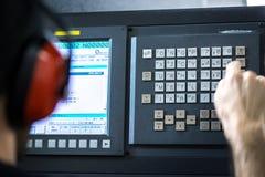 Cnc-operatör, på metall som bearbetar med maskin malningmitten i hjälpmedelseminariet som sätter in data med att bära för tangent Royaltyfri Foto
