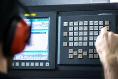 CNC operator, at metal machining milling center in tool workshop inserting data with keyboard wearing royalty free stock photo