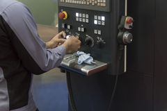 The CNC operator operate the CNC machine. Hand of operator turn the knob of CNC panel Royalty Free Stock Photography