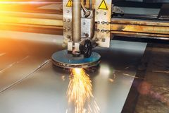 CNC programmable laser plasma cutting machine cuts sheet of metal with sparks. Modern industrial metalwork technology, professional manufacturing equipment stock images