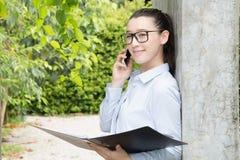 Современная бизнес-леди в офисе с космосом экземпляра говоря смартфон и удержание документов в руках Офис просторной квартиры отк стоковое изображение rf
