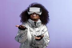 Современная курчавая коричнев-с волосами девушка одетая в цвета серебр куртке использует представления стекел виртуальной реально стоковая фотография rf