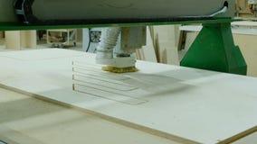 Современная машина woodworking в действии Режет курчавые части от листа переклейки Продукция деревянной мебели акции видеоматериалы