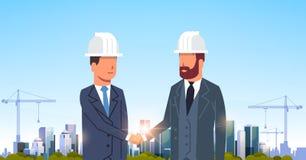 Согласование рукопожатия 2 построителей бизнесменов во время встречи над построением кранов башни строительной площадки города иллюстрация штока